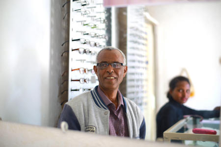 The next day, Gebre visits an eyeglass shop to try on some reading glasses and sunglasses.